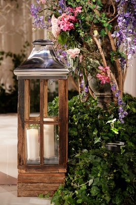 wooden lantern with chrome top and two pillar candles, ivy display with purple and pink flowers