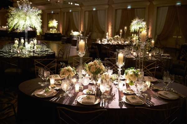 Round tables with tall dendrobium orchid flowers and oval tables with tall candles and orchids rose