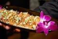 miniature crispy taco appetizers with filling served on black tray with purple orchids