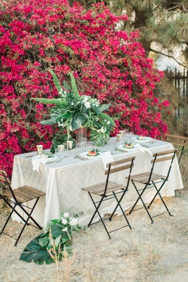 rustic chic styled shoot table champagne linen deck chairs foliage bougainvillea wall