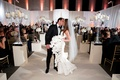 Chad Carroll kisses Jennifer Stone at wedding ceremony bride wears Oscar de la Renta orchid bouquet