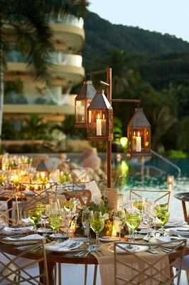 Outdoor poolside wedding reception with rustic centerpieces