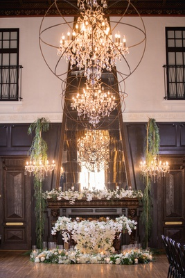 ebell long beach wedding, sweetheart table covered in orchids in front of fireplace