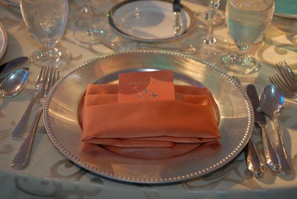 Wedding reception menu in the form of an orange passport in napkin