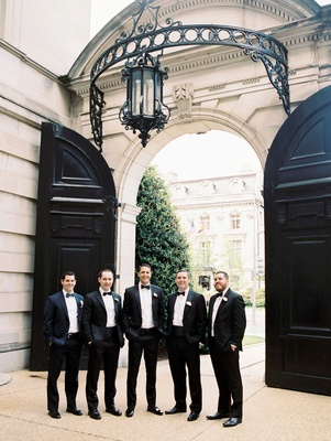 Groom with friends and family all in tuxedos and bow ties at luxe venue in washington dc