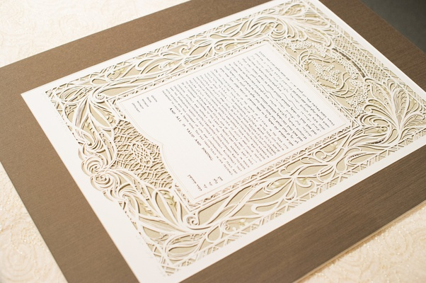 White ornate ketubah on wooden board for Jewish wedding