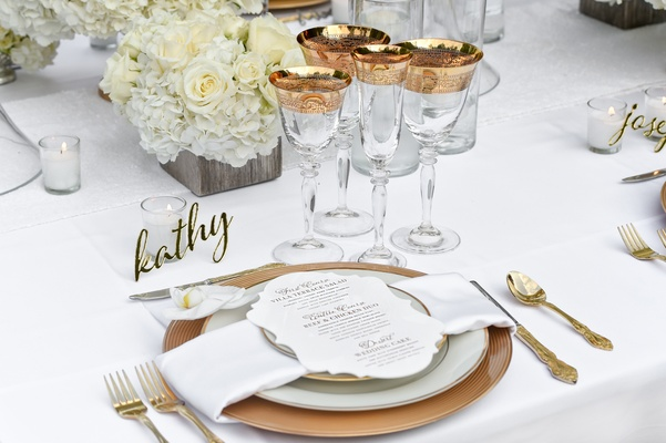 wedding place setting with gold laser cut place setting, gold chargers, gold flatware, and an orchid