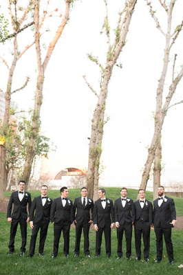 Cute men in tuxes standing in green grass