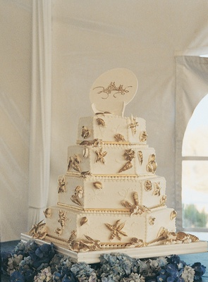 White wedding cake with gold starfish and seashells