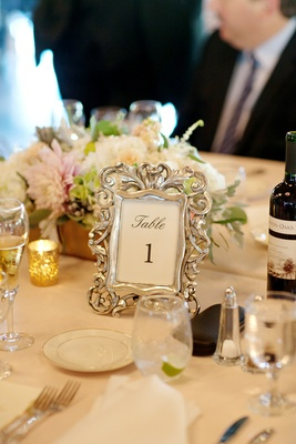 Wedding reception table with table number in ornate silver frame