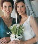Bride and her mom hold the bouquet together