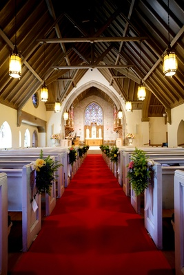 Red carpet runner between pews at church wedding ceremony in Illinois stained glass