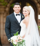 Bride in lace dress Martina Liana holding garden bouquet of flowers and greenery groom in tuxedo bow