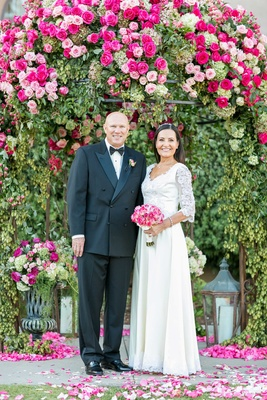 Vow renewal husband and wife under pink rose pergola with wedding dress pink bouquet tuxedo