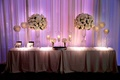 Purple uplighting on curtain behind escort card table with white rose and hydrangea flower arrangeme