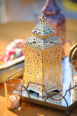 a small gold lantern with a unique design on a reflective surface next to small low candles