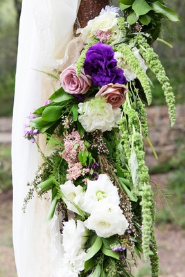 Pink roses, white and purple flowers, greenery, amaranthus on rustic outdoor wedding ceremony altar
