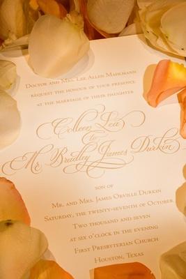 Gold script wedding invitation with orange rose petals