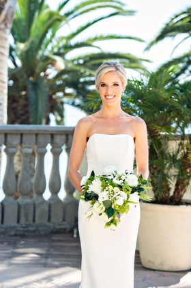 bride in strapless ines di santo wedding dress bouquet of white flowers greenery palm trees