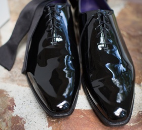 groom's shiny black dress shoes with bow tie and black and gold cuff links