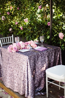 Wedding reception sweetheart table with purple sequined tablecloth and roses by leafy hedge