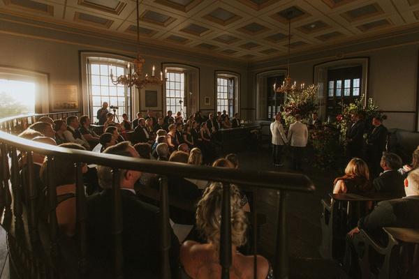 wedding ceremony colony house newport rhode island sunlight dark chandelier moody flowers