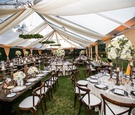 wedding reception alabaster drapery tent venue wood table round tables white centerpiece