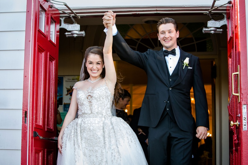 Bride in wedding dress ball gown from kleinfeld bridal cap sleeves jewels bow tie on groom hands up