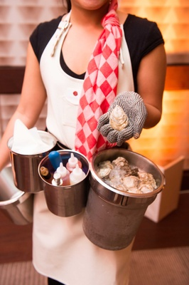 Server shucking oyster shells at cocktail hour with sauces and oysters in tin pails