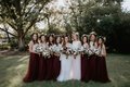 Bridesmaids with white bodices and burgundy skirts flower crowns and bouquets maid of honor in white