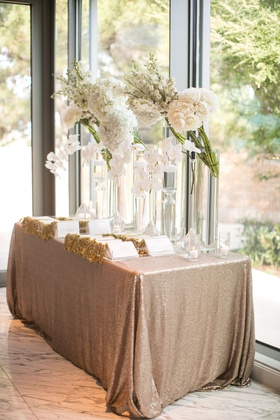 wedding welcome table gold sequin linen ceremony programs white flowers tall glass vases rose orchid