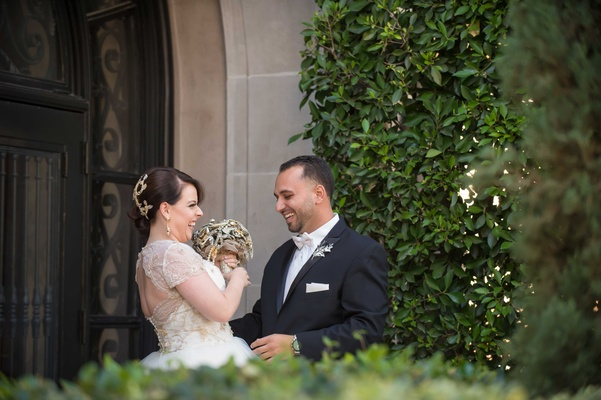 Bride in gold ball gown with jewel bouquet smiles with groom during First Look in courtyard
