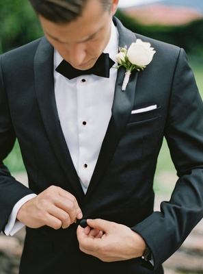 groom in calvin klein suit with bow tie white pocket square and white rose boutonniere buttoning