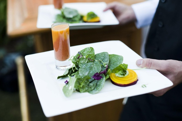 Caterer holding two plates of salad appetizer