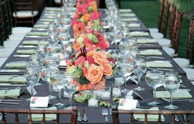 Long wedding reception table lined with vibrant flower arrangements