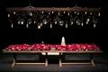wooden table with long pink floral arrangement under unique geometric lighting concept bulbs