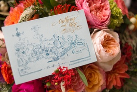 place card with map placed on pink flowers