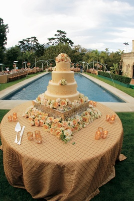 wedding cake surrounded by orange and white flowers