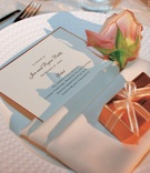 White menu card rimmed in gold with favor box