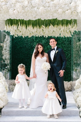 Bride and groom with two flower girls holding hands with child baby's breath flower crown tights