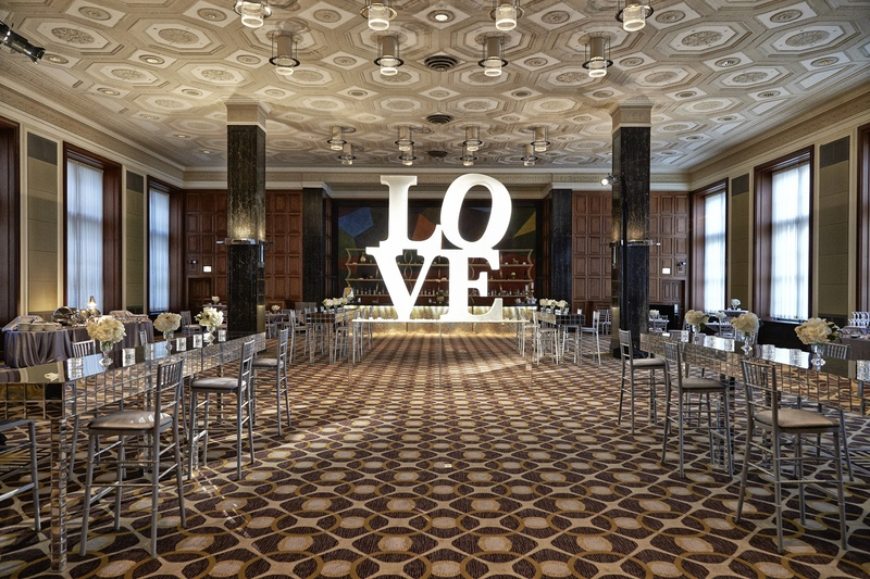 LOVE sign in room filled with silver chairs