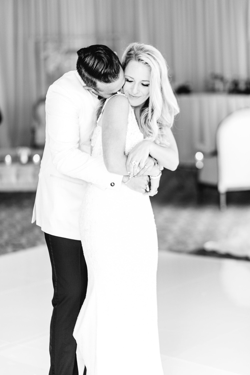 Black and white photo of bride and groom on dance floor hugging groom kissing bride neck reception