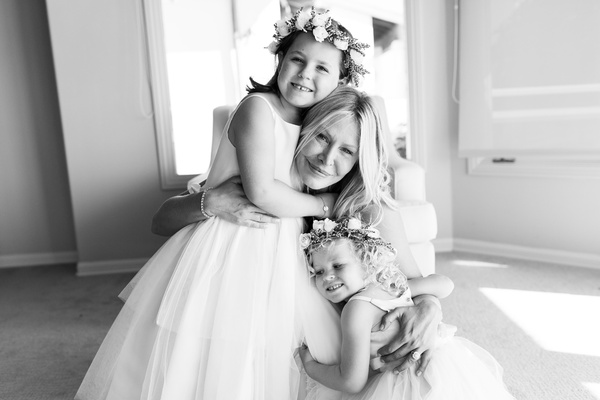 black and white photo of bride hugging flowers girls, bride with future stepchildren, blended family