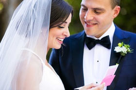 bride opens pink letter and reads it in front of her groom before their ceremony