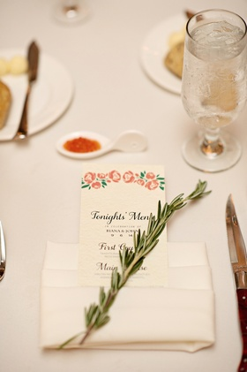 Wedding reception with menu decorated with pink flowers in cream napkin, rosemary sprig