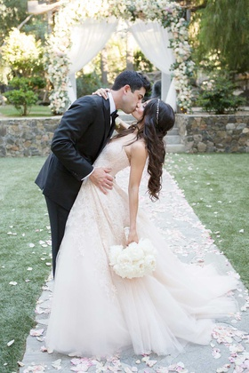 bride in blush monique lhuillier wedding dress and jeweled headband, groom in suit, dipped for kiss