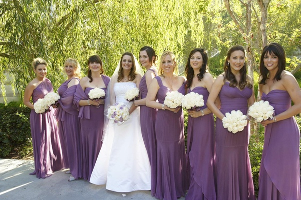 Bride with bridesmaid carrying white rose bouquets