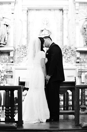 Black and white photo of couple kissing at altar
