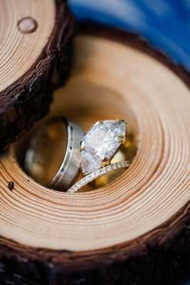 Yellow gold diamond engagement ring with three stones, diamond wedding band, and groom's band