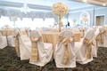 Wedding reception with tables covered in gilt tablecloths, chairs in vanilla seat covers, gold bows